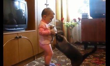 Η γάτα προσπαθεί να πάρει το μωράκι της από το κοριτσάκι