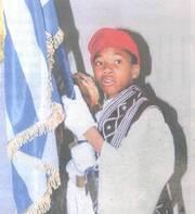 Ντυμένος τσολιάς, κρατούσε με καμάρι την ελληνική σημαία.